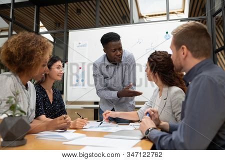 Diverse Colleagues Busy Brainstorming Discussing Paperwork At Briefing