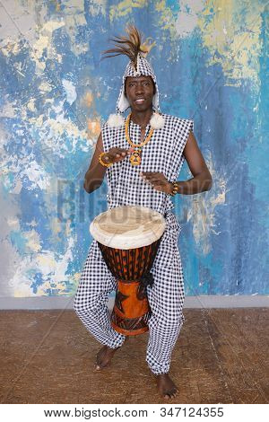 African Artist In Traditional Clothes Playing Djembe Drum