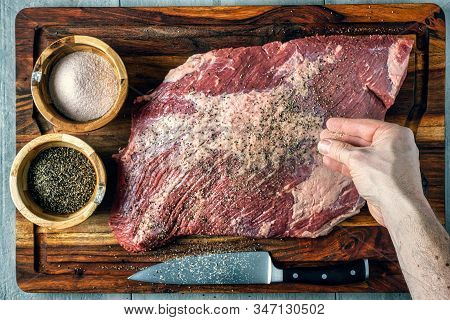 Seasoning A Beef Brisket With Salt And Pepper Before Barbequing On A Smoker