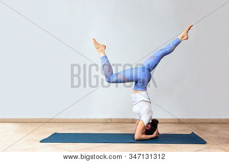 Yogi Girl Standing In Adho Mukha Vrksasana Exercise. Woman In Headstand Practicing At Yoga Studio. D