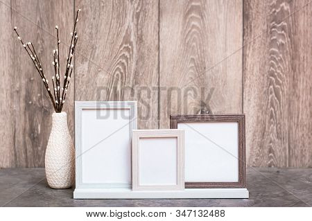 Ready Mock Up. Three Empty Photo Frames On The Stand And A Vase With Artificial Willow Branches Are