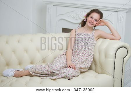 Beautiful Young Girl Sitting In The Studio On The Couch Near The Fireplace Style And Fashion Concept
