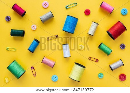 Spools Of Colored Thread, Buttons And Safety Pins On Yellow Background