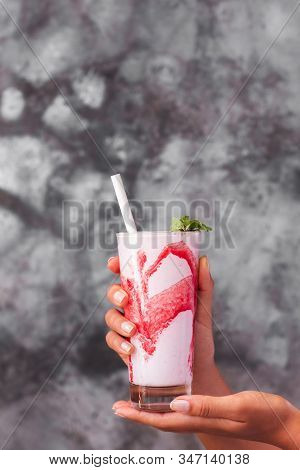 Glass Of Fresh Cold Frappe Or Milkshake With Red Strawberry Syrup In Woman Hands On Background Of Gr