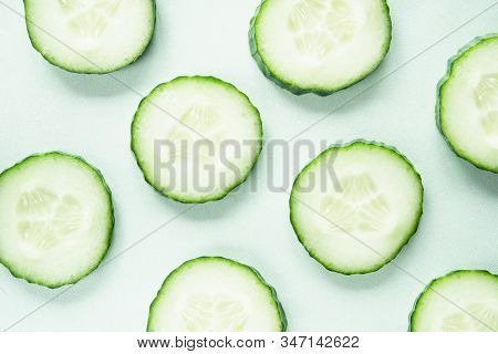 Pattern With Freshly Cut Cucumber Slices On Green Background