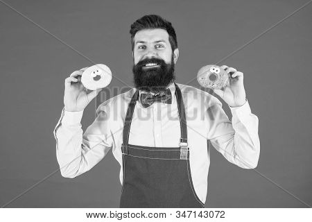 Baked Donuts With Funny Faces. Happy Baker Holding Home Baked Snack On Red Background. Hipster Smili