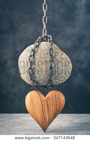 Stone Hanging On Chain Over Wooden Heart. Unhappy Or Feels Depressed Concept. Russian Idiom Illustra