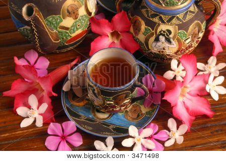 A Pot And Cup Of Tea With Flowers
