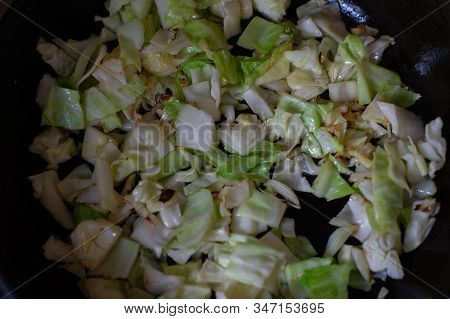 Vegetables Cut In Cubes Fried On Frying Pan, In Kitchen. Cabbage Fried In Cubes In A Pan. Vegetarian