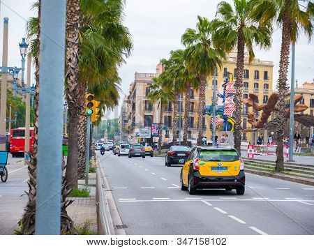 Barcelona, Spain. May 2019. Passeig De Colom, A Wide Avenue Lined With Palm Trees, With A Red Bridge