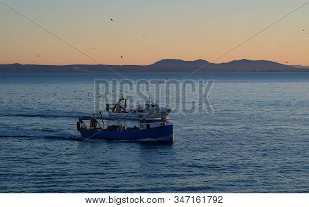 The Fishing Boats Return To The Port In The Evening After A Working Day. Vessels Or Ships Are Sailin