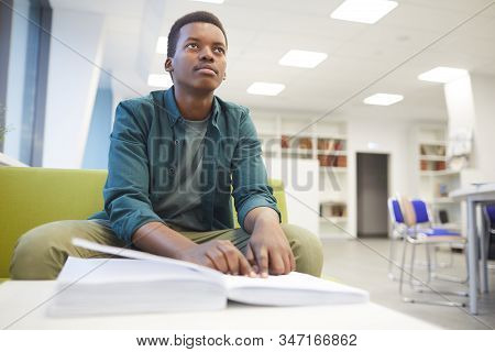 Portrait Of Young African-american Man Reading Braille While Studying In School Library, Copy Space