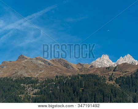 The Tops Of The Mountains With Two Paratroopers In The Blue Sky. Panoramic View