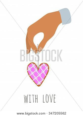 Happy Valentines Day. Hand Holding A Gingerbread On A Thread With Icing In The Shape Of A Heart. Iso
