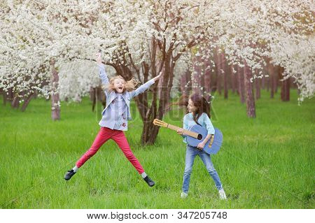 Ecstatic Live Outdoor Rock Music Concert By Two Little Young Girls Jumping Singing And Playing Guita