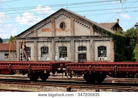 Railway Wagon Composition In Front Of Old Railway Station With Dilapidated Walls And Broken Windows