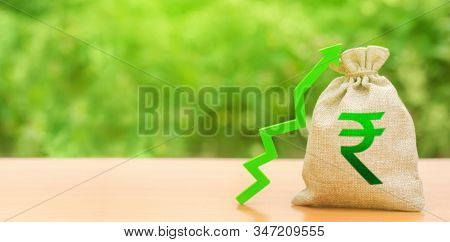 Indian Rupee Money Bag And A Green Arrow Up. Stability, Prosperity. Strengthening Of National Curren
