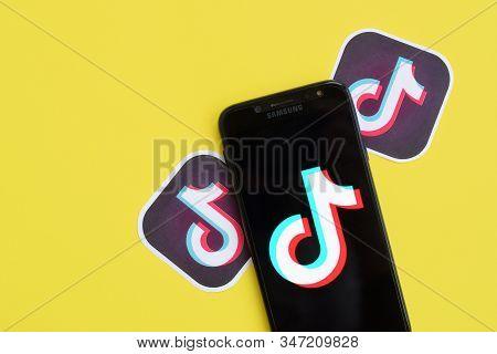 Tiktok Logo On Samsung Smartphone Screen On Yellow Background. Tiktok Is A Popular Video-sharing Soc