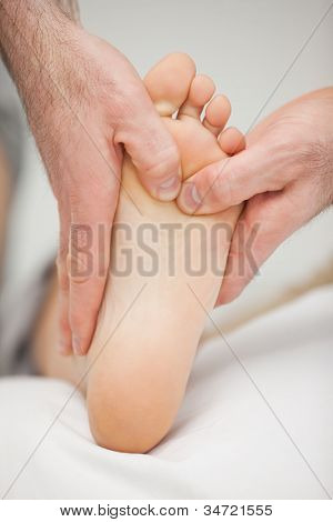 Chiropodist massaging the foot of a patient in a medical room