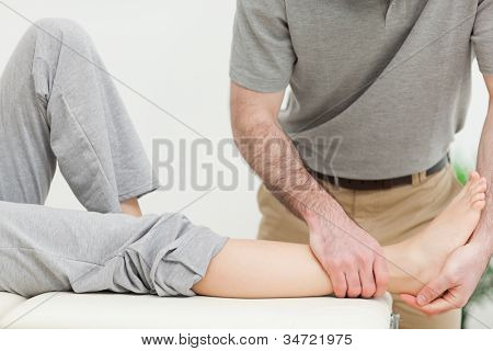 Close up on a doctor examining the foot of a woman in a bright room