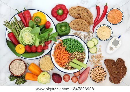 Low GI diet food for diabetics with blood sugar testing device with foods high in vitamins, minerals, antioxidants & smart carbs. Below 55 on the GI index with corresponding values. Top view.