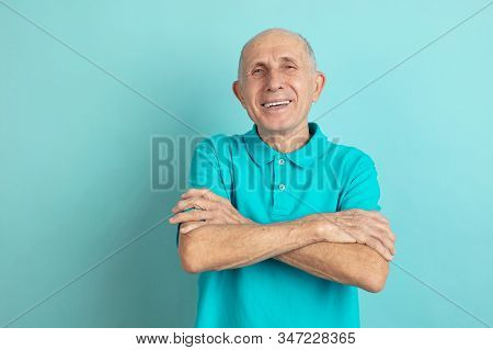 With Hands Crossed. Caucasian Senior Mans Portrait Isolated On Blue Studio Background. Beautiful Mal