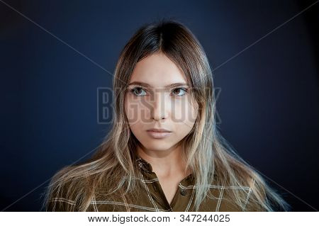 Young White Woman Looks Away, Close-up On Intensely Blue Background. Female Caucasian Ethnicity, 22