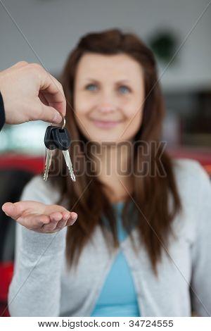 Happy brunette receiving car keys in a garage