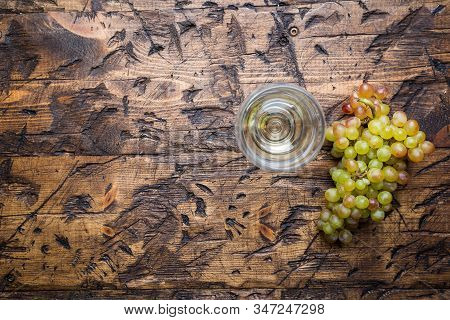 Glass Of White Wine And Ripe Grapes On Wooden Background, Top View