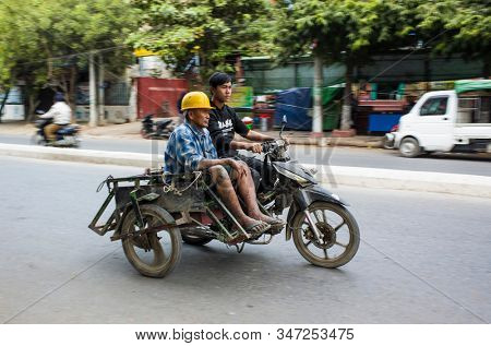 Mandalay, Myanmar - January 3, 2020: Man in yellow helmet is sitting on old sidecar motorbike on street with blured background. Motor bike with panning photo effect and motion blur