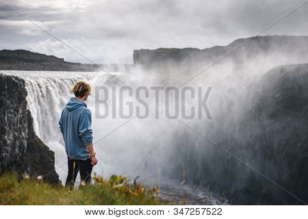 Young Hiker Standing At The Edge Of The Dettifoss Waterfall Located On The Jokulsa A Fjollum River I