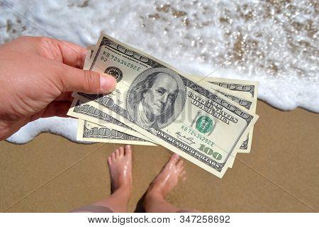 Girl Holding Money Bill Of 300 Dollars On Background Of Sea Ocean