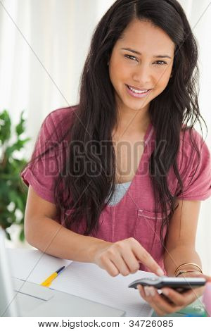 Smiling brunette student using a calculator to do her homework poster