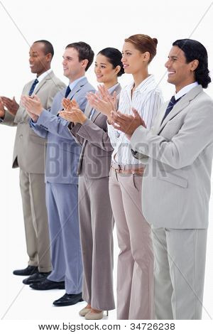 Business people smiling and applauding while looking towards the left side against white background