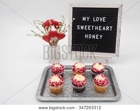 My Love, Sweetheart, Honey Spelled Out On Letter Board In White Text With A White Vase Filled With G