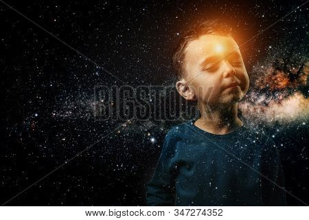a small child whose light shines in his forehead. He imagines himself an astronaut. Elements of this image furnished by NASA