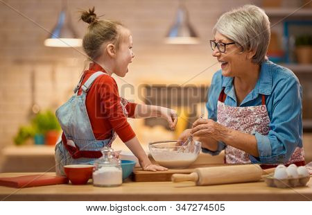 Happy loving family are preparing bakery together. Granny and child are cooking cookies and having fun in the kitchen. Homemade food and little helper.