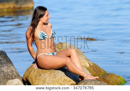 Young Tan Girl In Swimsuit, Smiling And Posing While Lying On Back On Boulder On Seashore