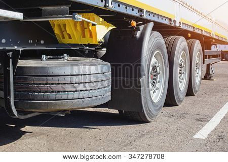 Three-axle Cargo Trailer With New Wheels And A Spare Wheel, Background. Shipping And Logistics, Secu
