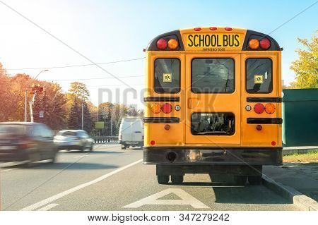 Big Classic Vintage American Yellow Schoolbus Standing On A Bus Lane At Highway And Waiting Pupils A