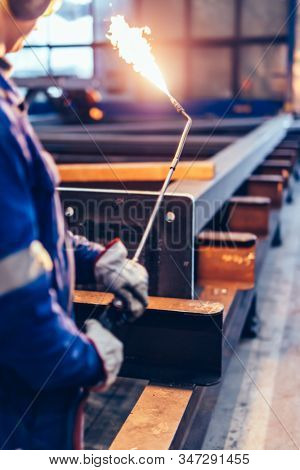 Worker operating acetylene torch in big factory. Heavy industry, shipyard