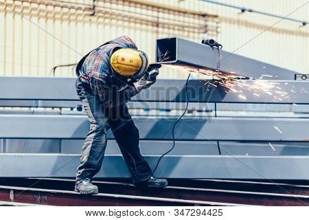 Worker grinding a steel profile in factory. Heavy industry at shipyard