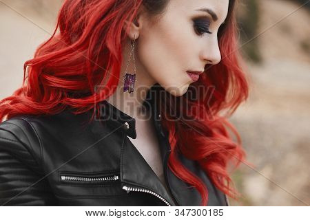 Fashionable Close-up Portrait Of A Model Girl With Red Hair And Trendy Makeup In A Leather Jacket. C