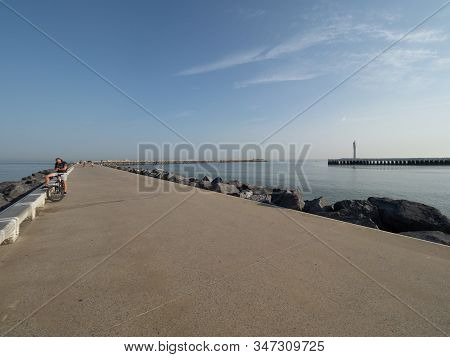 Ostend, Belgium - 7 August 2018: A Cyclist On The Western Breakwater In Ostend.