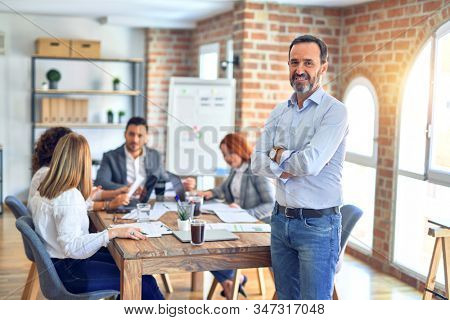 Group of business workers working together. Middle age handsome businessman standing smiling happy looking at the camera at the office