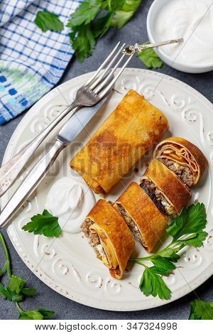 Pancakes Stuffed With Meat, Onion And Egg With Sour Cream. Traditional Russian Dish For A Shrove. To