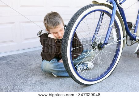 Sad boy depressed about his flat tire on his bicycle