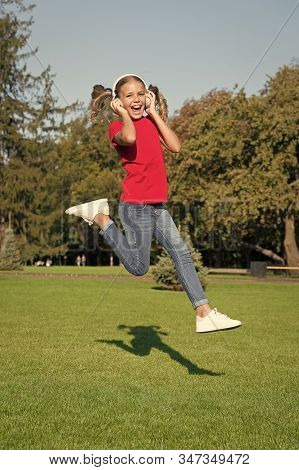Active And Dynamic. Active Child Jump Over Green Grass. Happy Little Girl Move Active To Music. Ener
