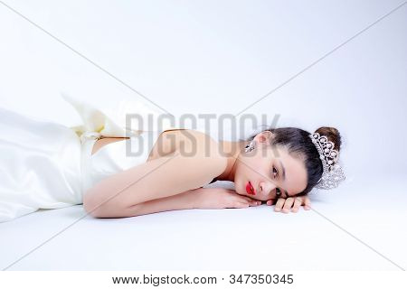 Beautiful Young Bride In White Wedding Dress Indoors. Luxuty Model Lying Over White Backgroung. Girl