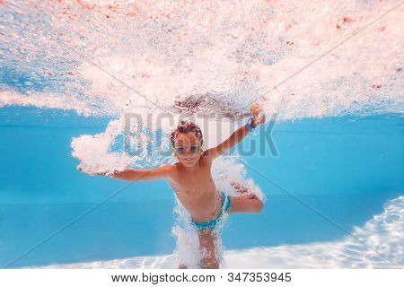 Happy Little Boy Splash Into The Pool After Jump Making Many Bubbles, Smiling And Wearing Swimming G